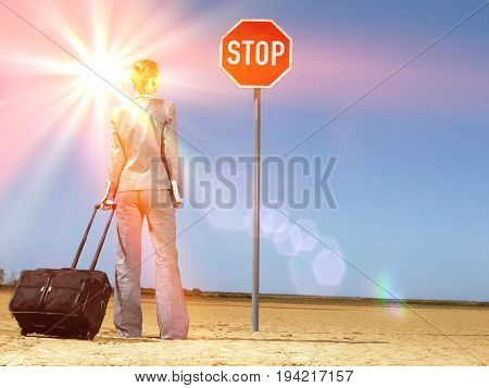 Rear view of young businesswoman with luggage looking at stop sign