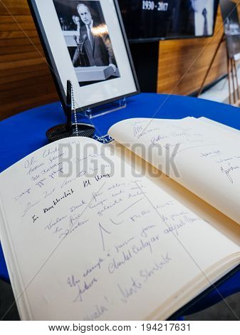 STRASBOURG FRANCE - JUL 1 2017: The messages in diverse languages of high ranked officials on the book of condolences next to a portrait of late former German Chancellor Helmut Kohl at European Parliament. Kohl who was Christ democrat or CDU party member