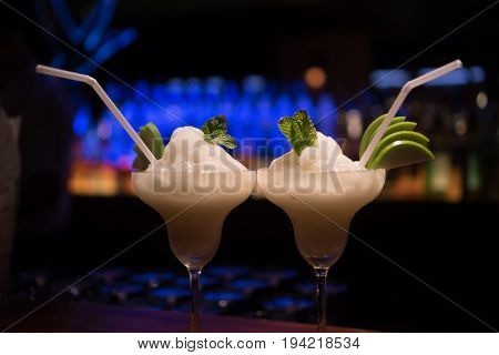 Closeup of two alcohol fruit coctail drinks on the table over blurred  bar restaurant background