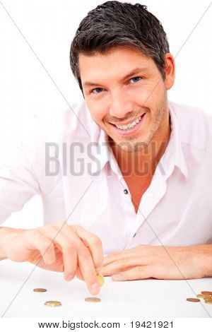Cheerful smiling casual man putting money coins on desk table to tower