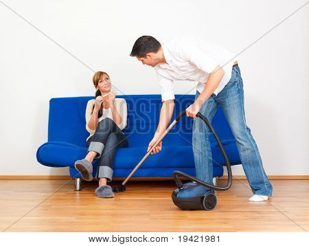 House and home apartment cleaning man while girlfriend is relaxing