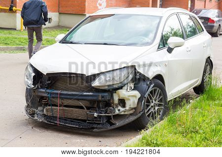 broken white car after the accident With a broken bumper
