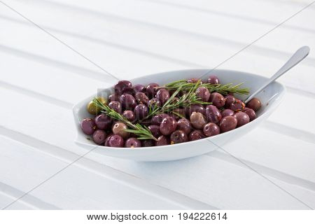Olives garnished with rosemary in white bowl