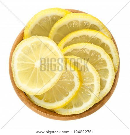 Lemon slices in wooden bowl. Fresh cut ripe yellow edible citrus fruit discs. Citrus limon Osbeck. Isolated macro food photo close up from above on white background.