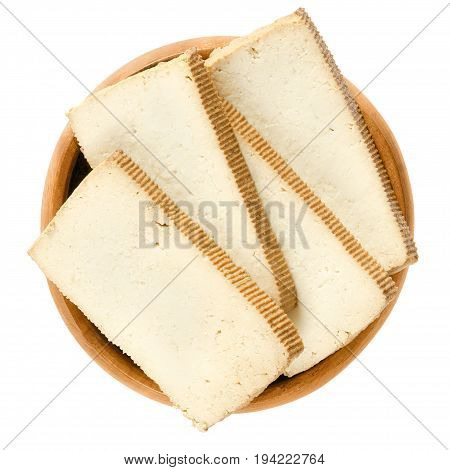 Smoked tofu slices in wooden bowl. Bean curd. Coagulated soy milk, pressed into firm white blocks. Component of Asian cuisine. Meat substitute. Isolated macro food photo close up from above over white
