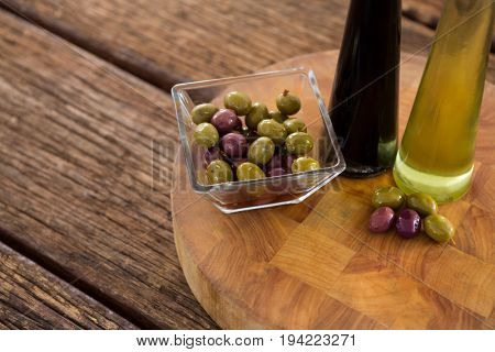 Close-up of marinated olives with balsamic vinegar bottles on table