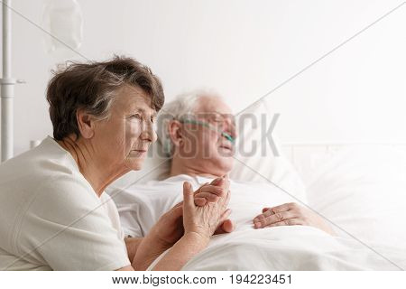 Sad senior woman sitting next to her dying husband in hospital