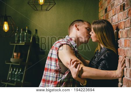 Couple kissing in the kitchen after romantic dinner