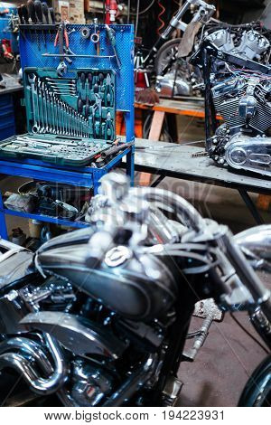 Background image of empty mechanics garage with opened toolbox set for motorcycle repair works