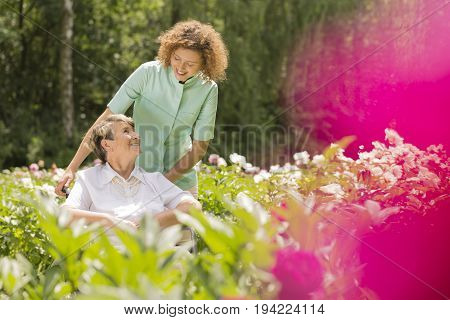 Senior woman on a wheelchair and looking at her young nurse surrounded by flowers