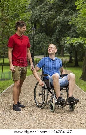 Man in wheelchair spending time in a park with his friend