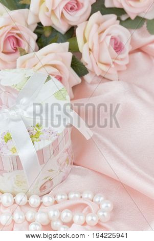 pink roses round gift box and a pearl necklace on a silk fabric