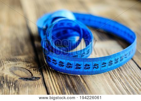 Blue Measuring Tape On Wooden Background