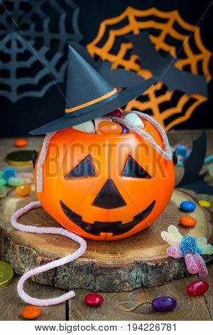 Halloween Jack o Lantern bucket overflowing with candy spooky Halloween decorations on background vertical