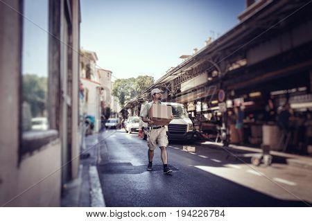Messenger delivering parcel, walking in street next to his van
