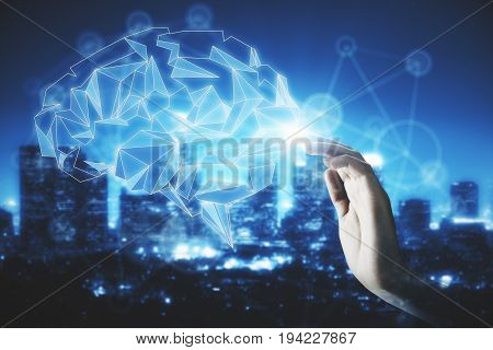 Hand touching abstract illuminated polygonal brain on night city background. Science concept. Double exposure