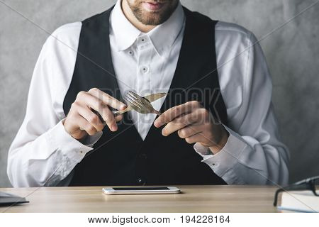 Crazy businessman about to eat smartphone with a knife and fork while sitting at wooden office desk with items