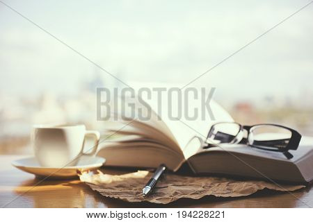 Windowsill with open book coffee cup glasses and paper sheet. Blurry city background with sunlight. Lifestyle concept