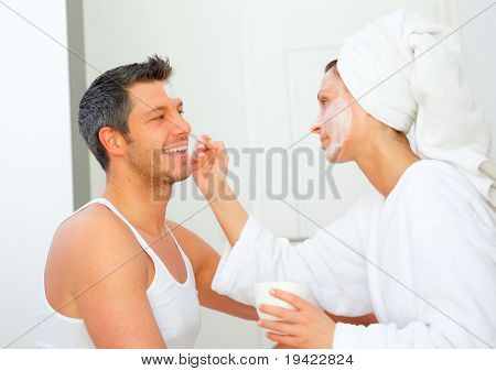 Dayspa couple applying cosmetic products eachother