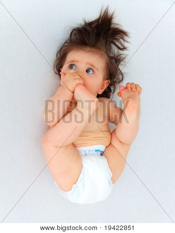 Funny baby looking lying on bed