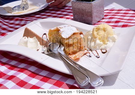 Strudel with a ball of vanilla ice cream and whipped cream
