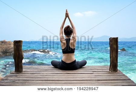 Healthy woman lifestyle exercising vital meditate and practicing yoga at seashore nature background. Healthy Concept.