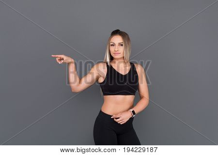 Blondy sporty woman in sporty outfit pointing finger standing against gray background.