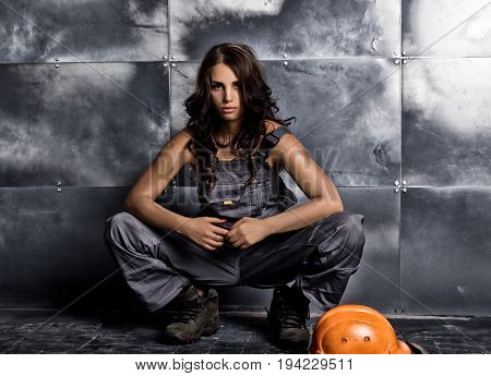 Beautiful sexy worker with a pickaxe and helmet. Seductive and beautiful woman miner sitting on a floor on steel background.