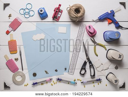 Top View Of Blue Pages And Layout Tools For Needlework And Scrapbooking On Wooden Boards With Copy S