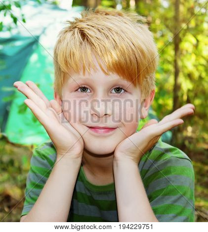 Boy is playing Peekaboo at forest camp summer scene outdoors