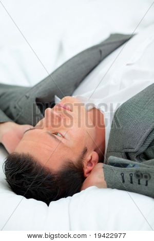 Business man relaxing while lying on hotel bed