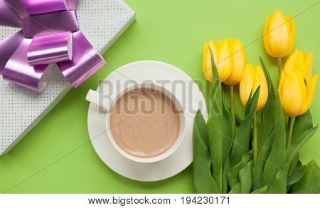 From above shot of cup with coffee on green table with yellow tulips and giftbox.