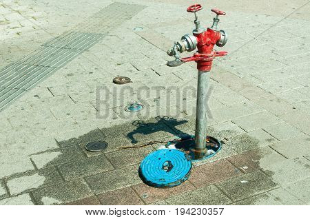Fire hydrant used like cooling refreshment water supply for hot summer days on the street in the city.