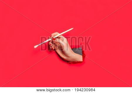 Anonymous female hand in hole of red paper holding paintbrush.