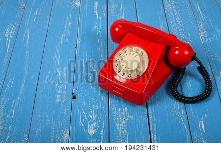 Vintage Phones - Red a retro telephone on a blue wood background.