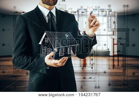 Businessman holding abstract house model and drawing on blurry interior background. Architecture concept. 3D Rendering