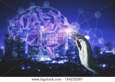 Hand touching abstract illuminated polygonal brain on night city background. Technology and knowledge concept. Double exposure