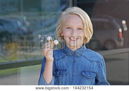 Beautiful cheerful school girl playing with a gold fidget spinner. A popular trendy toy.