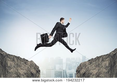 Side view of young businessman jumping over gap on city background. Risk concept