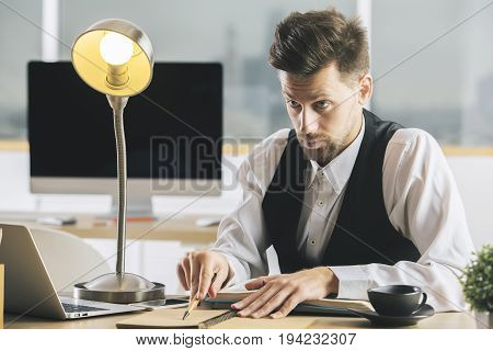 Crazy man with lamp interrogating someone at desk with coffee cup laptop supplies and other items