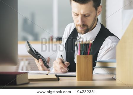 Portrait of attractive caucasian man accountant using calculator while sitting at office desk with devices and other items