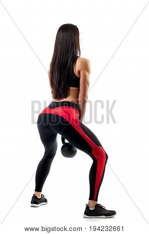 Young woman in sportswear makes squat with weight in in semi-squat position on white isolated background