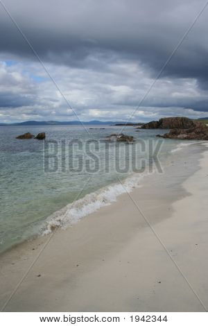white sand beach and dark storm clouds Iona Scotland poster