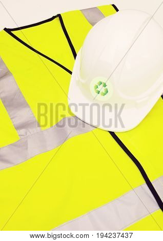 Safety vest and hard hat with recycling symbol over white background