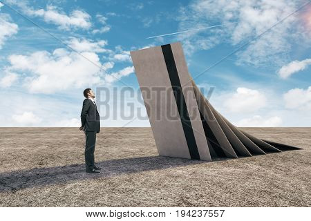 Thoughtful businessman with huge credit cards about to fall on him in desert with blue sky and sunlight. Crisis concept. 3D Rendering