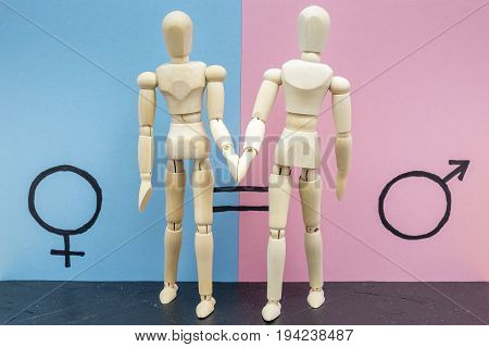 Two wooden dolls depicting a man and a woman holding hands next to the symbol of gender equality