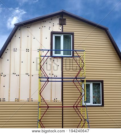 Beige siding panels mounting with scaffolding on beautiful rural house in sunny day front view