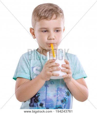 A cute little kid in blue t-shirt with a glass full of nutritious and organic milk isolated on a white background. Pretty little boy is drinking milk from a yelllow straw isolated on a white background.