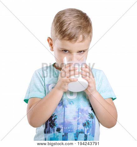 Adorable little kid is holding a glass of organic milk and drinking fresh milk isolated on awhite background. Close-up portrait of a cute little boy in a blue t-shirt with a full glass of milk.