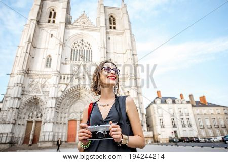 Young woman tourist walking with photo camera on saint Pierre square near the cathedral in Nantes city